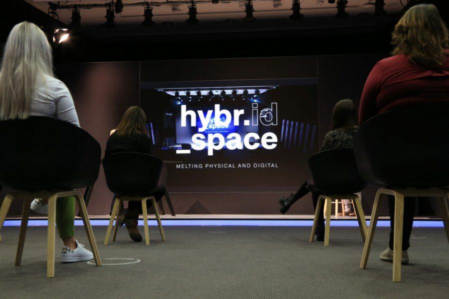 Froschperspektive Menschen sitzen auf Stühlen, vor einer Bühne mit einer LED Wand