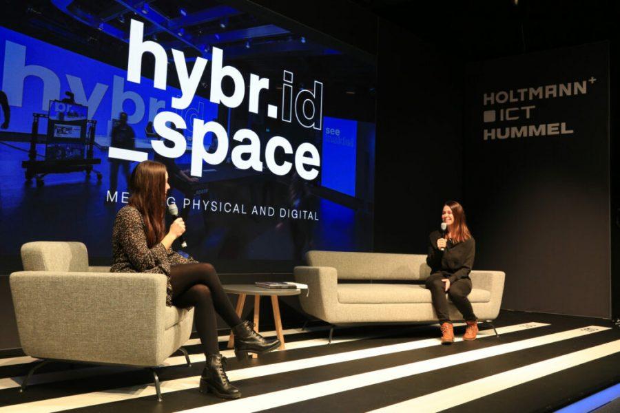 Zwei Frauen sitzen in Sesseln auf einer Bühne und unterhalten sich mit Micro undLED Wand im Hintergrund