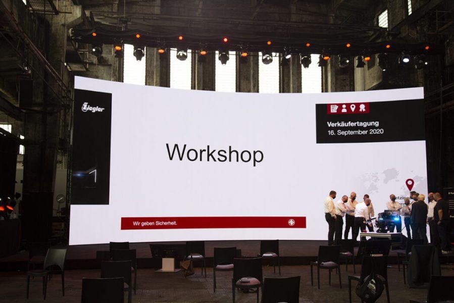 Menschen von Bühne mit weisser LED Wand im Hintergrund