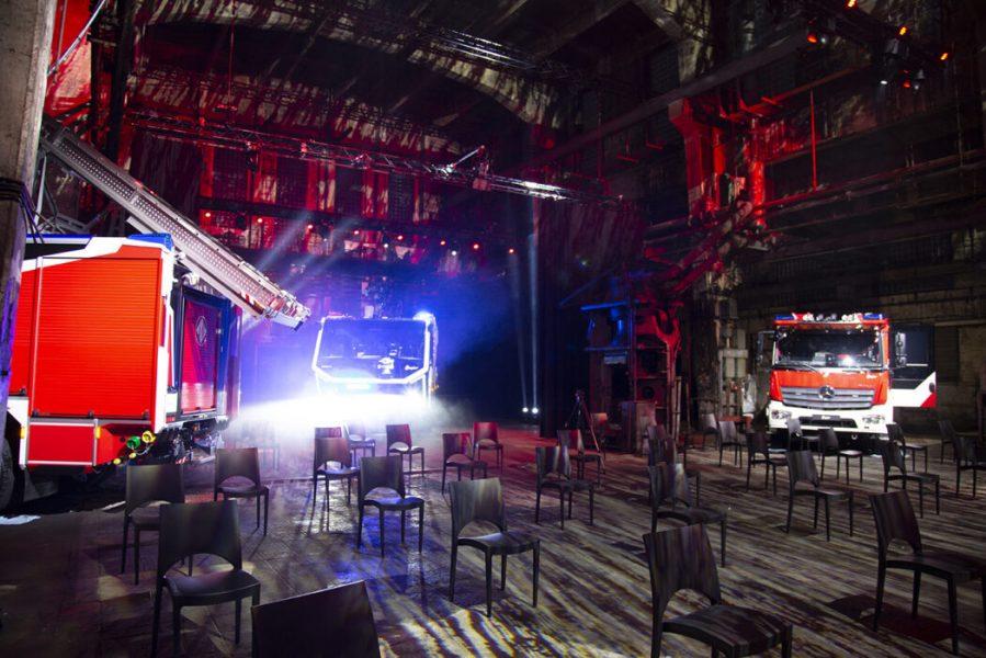 Beleuchtete Industriehalle mit Feuerwehrautos