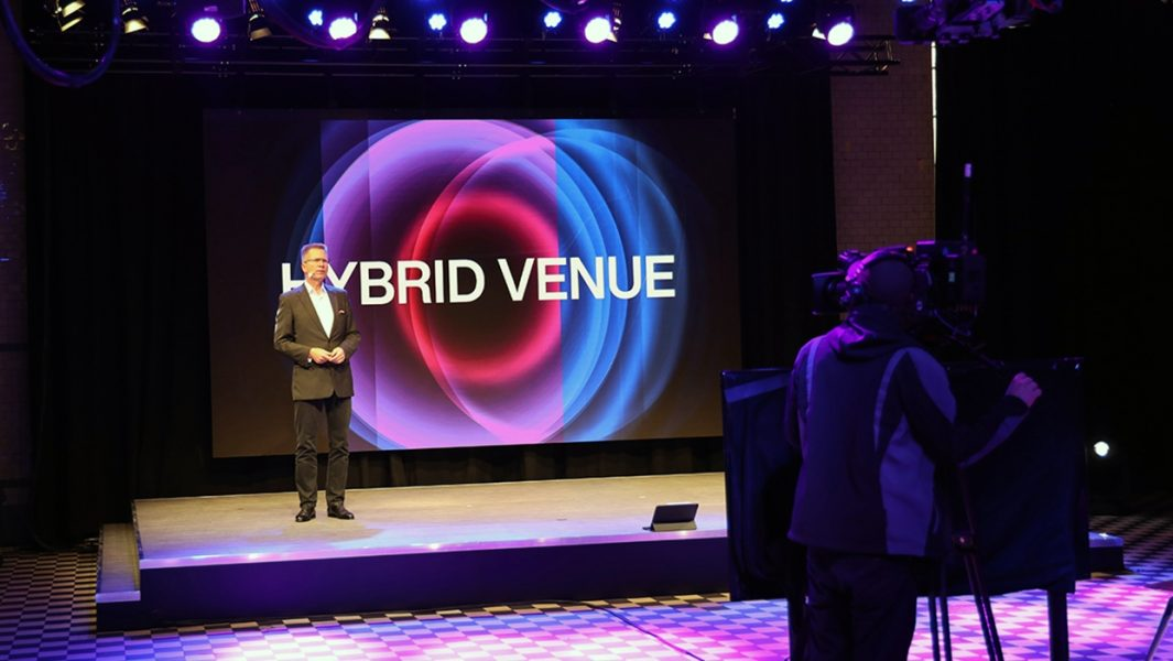 Erik Wolff auf der Bühne mit LED Wand in Hintergrund und Kameramann filmt ihn