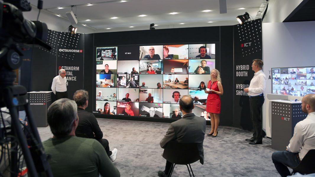 Mehrere Personen vor einer LED Wand auf der Teilnehmer einer Digitalkonferenz angezeigt wird