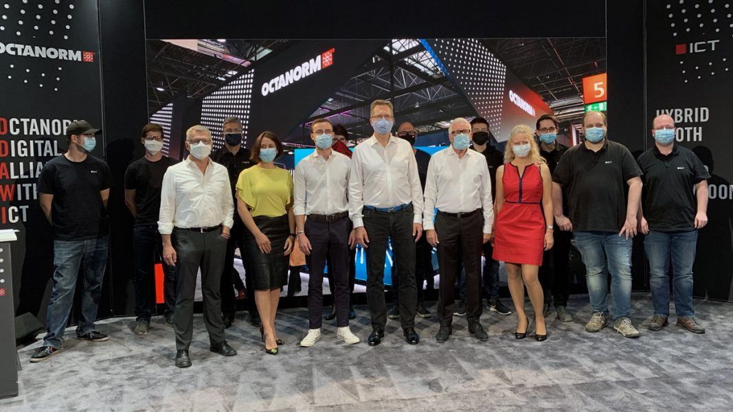 Mehrere Personen vor einer LED Wand mit Corona konformen Masken