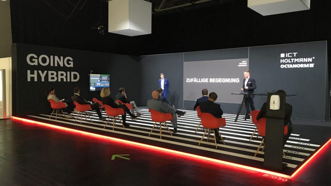 Messestand mit roten Stühlen, Publikum und LED Wand