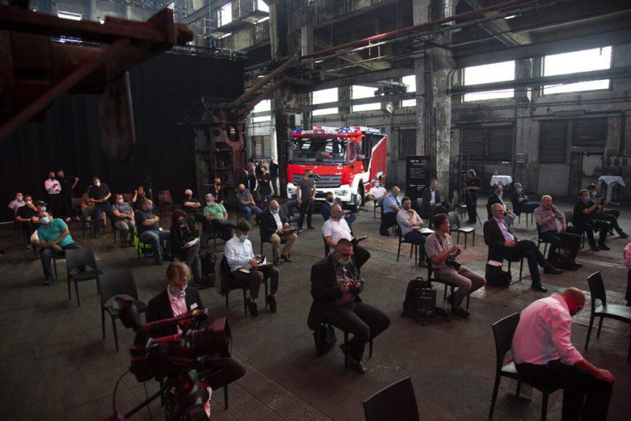 Event in einer Industriehalle mit Zuschauern und Feuerwehrauto