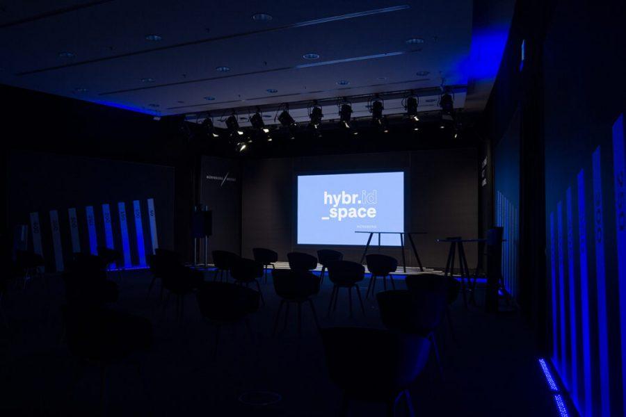 Leere Bühne mit Stühlen davor und blauer LED Wand im Hintergrund