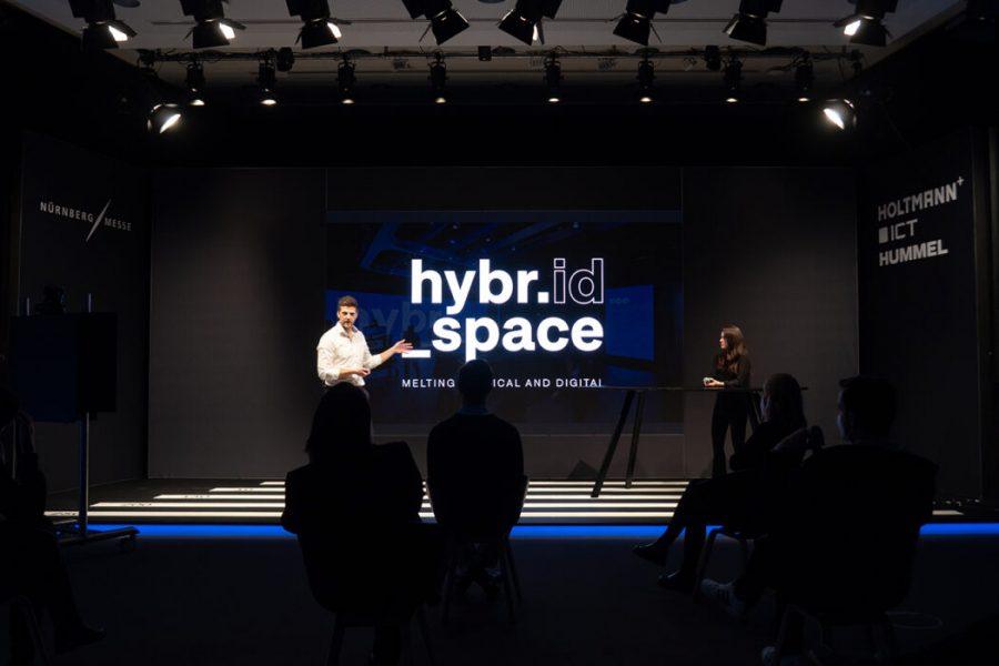 zwei Menschen präsentieren den Hybrid Space auf der Messe Nürnberg