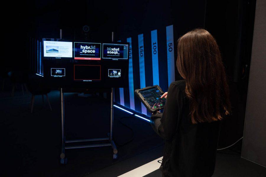 Frau mit Tablett steht vor Monitor und steuert die Kameras