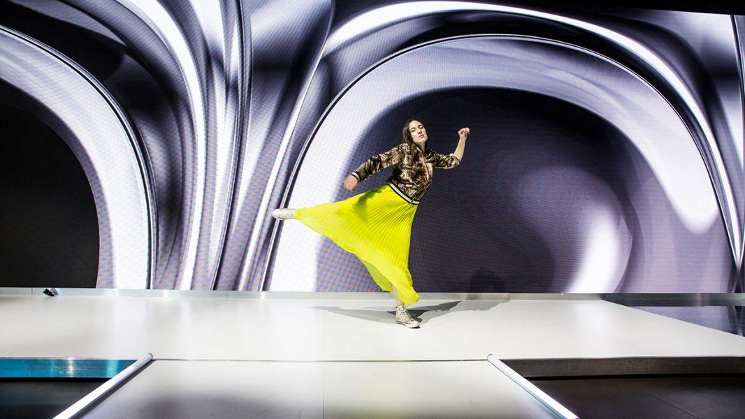 Moderne Frau tanzt vor einer interaktiven LED Wand
