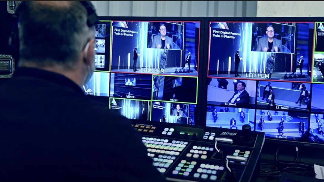 Regietechniker vor Bildschirmen und einem Mischpult